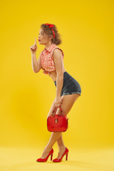 Stylish girl in red heel shoes with small red bag .