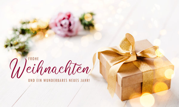 Romantic, golden christmas gift box with bright, light background and feminine, pastel colors / banner, header and elegant greeting text in german language