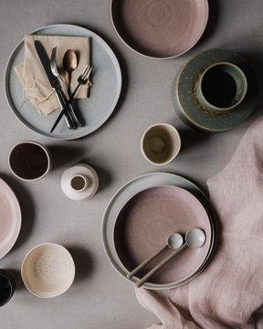 Flatlay von Keramiktellern und Tassen und Vasen und Löffeln, der Tisch wird gedeckt