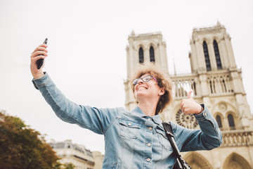 Tourist in Paris making funny selfie near Notre Dame Cathedral. Beautiful young Caucasian tourist woman with backpack in Paris making funny selfie hand holding phone, photo near Notre Dame Cathedral