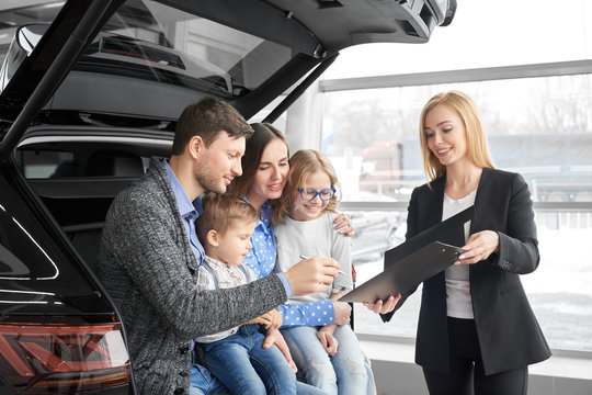 Happy family buying new comfortable black car in auto salon