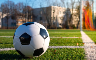 Shot of a corner kick. A black and white ball lies in the corner of the football field.