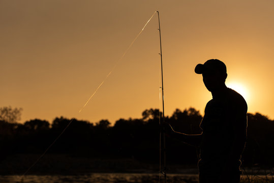 A fisher stands at his fishing spot on the White River in Indianapolis