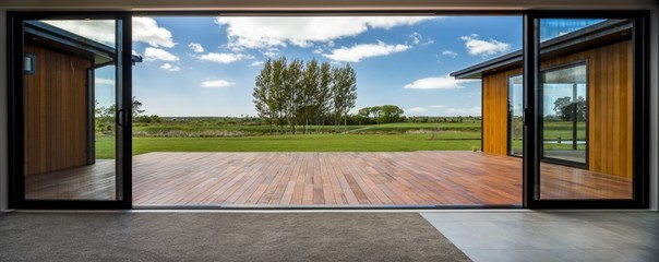 View from a modern house with big glass doors looking at the green field