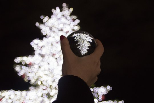 Person holding a crystal ball with the reverse reflection of the illuminated white Christmas tree