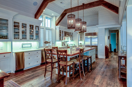 Large expensive chefs kitchen in luxury home with rough hewn wood and white cabinets.