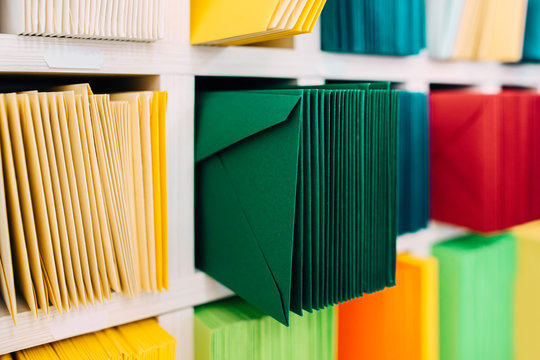 Various sort mail envelopes arranged on a shelf by color and type categories.