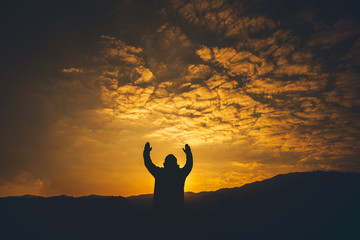 Man lift hands and Praying at sunset background. christian silhouette concept.