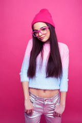 young pretty brunette girl posing on pink backgroundwearing glasses and hat, lifestyle people happy...