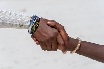 Tribal masai men making handshake in the tropical beach on island Zanzibar, Tanzania, Africa, close up
