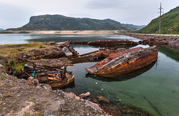 Papiers peints Navire Cemetery of old ships on the shore of the Barents Sea at low tide - the wrecks of ships, water and algae