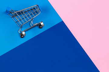 Mini shopping trolley cart on pastel pink, light blue and navy color background. Online shopping, buy, sale, discount concept