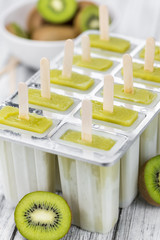 Wooden table with Kiwi Popsicles (detailed close-up shot; selective focus)