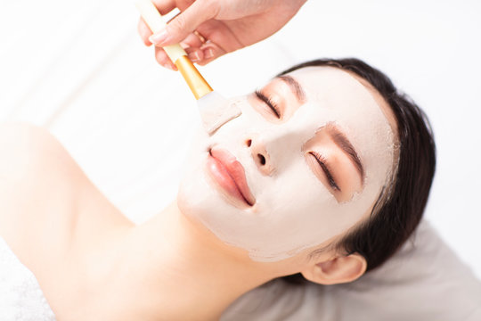 young Woman with mask on face in spa beauty salon