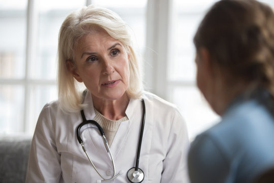 Middle-aged female doctor talk examine little patient