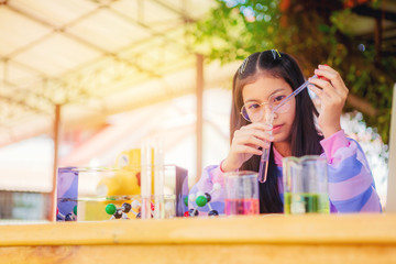 Asian teenage girl in elementary science class doing chemical experiment test try to drop color water to test tubes. Education concept. Selected focus