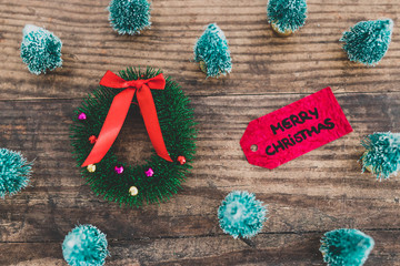 festive season's decorations group of miniature Christmas trees with wreath and Merry Xmas label among them