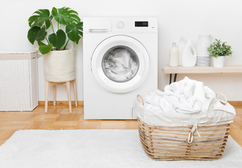 Laundry in washing machine and basket, interior of pastel colors