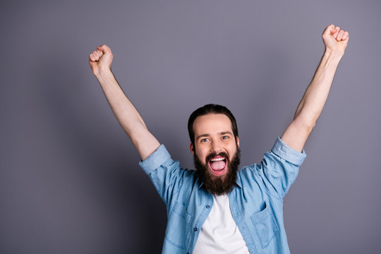 Yeah we win. Active football lover guy watch match his favorite team victory feel delighted crazy emotions raise fists scream yeah wear stylish clothes isolated over grey color background