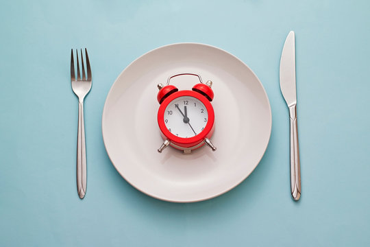 Red alarm clock on a clean white dinner plate