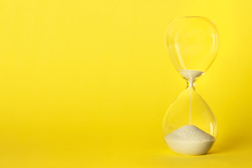 An hourglass with oozing sand on a vibrant yellow background with a place for text