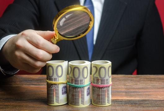 A businessman inspects a euro money bundle rolls through a magnifying glass. Search investments, projects financing Sources. Financial monitoring, fight money laundering. Favorable deposits offers