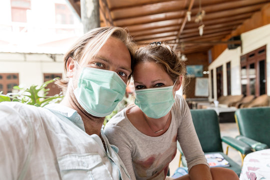 Beautiful portrait selfie of tourists with face masks sheltering for volcanic ash in Sumatra, Indonesia