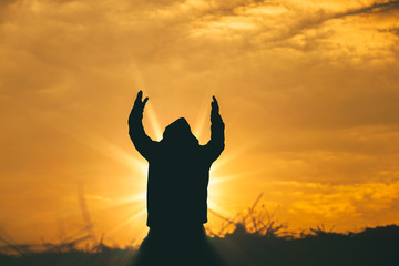 Man raise two hands to sky for praying to God at sunset background. christian silhouette concept.