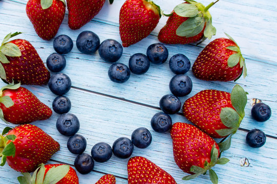 Blueberry and strawberry heart on a wooden background. Valentines day concept