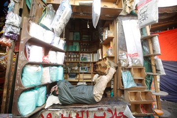 A vendor rests in his store at a market place in the old quarter of Sanaa