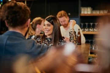 Young handsome caucasian couple standing in bar, chatting and flirting and having great time.