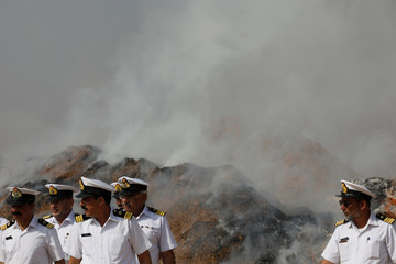 Officers from Pakistan Customs walk in front of a burning pile of betel nuts as they attend a ceremony to destroy confiscated contraband and goods unfit for human consumption on the outskirts of Karachi