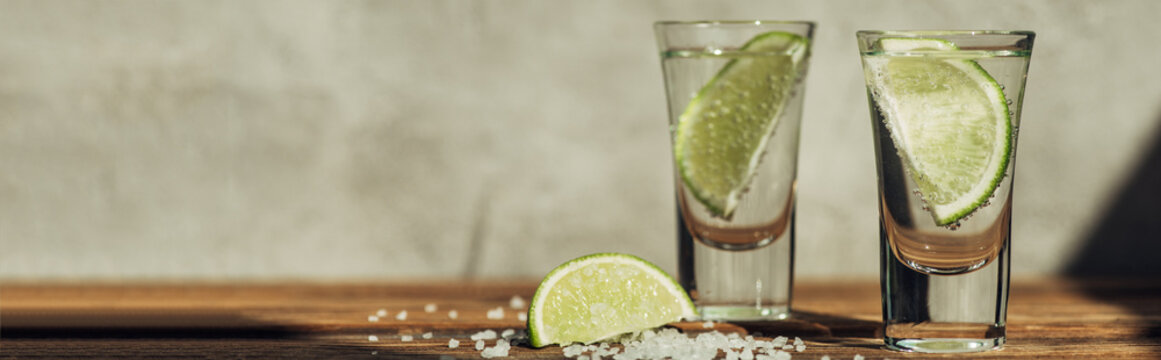 fresh tequila with lime and salt on wooden surface in sunlight, panoramic shot