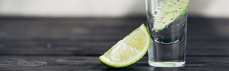 fresh tequila with lime on wooden surface, panoramic shot
