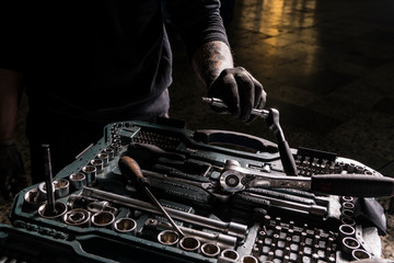 Detail of the hands of a mechanic taking a screwdriver from a toolbox