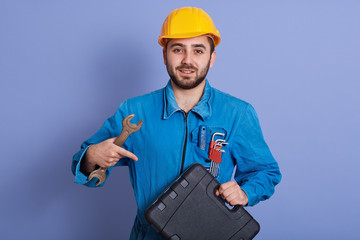 Half length portrait of bearded guy holding wrenchin hand and pointing with his forefinger at tool box in other hand, posing isolated over blue background, looks calm, dresses uniform and helmet. Wall mural