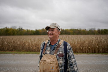 Abe Hodgen stands in front of a corn field on his farm in Roachdale