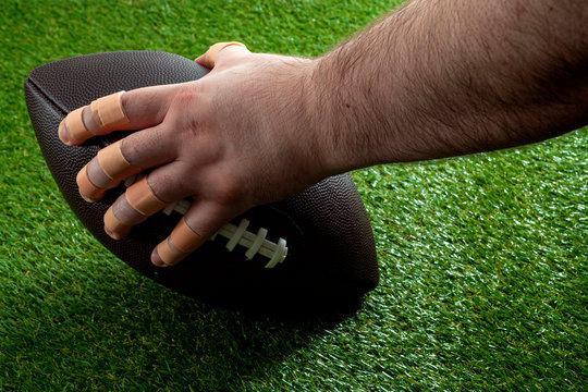 American football game at night under the spotlight conceptual idea with offensive lineman hand with bandaged fingers holding the ball and getting ready to snap the play