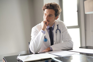 Portrait of doctor being thoughtful about diagnosis
