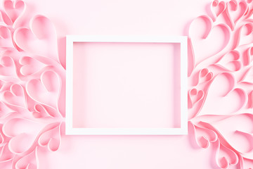 Pink paper hearts with white picture frame on Light pink pastel paper background. Love and Valentine's day concept.