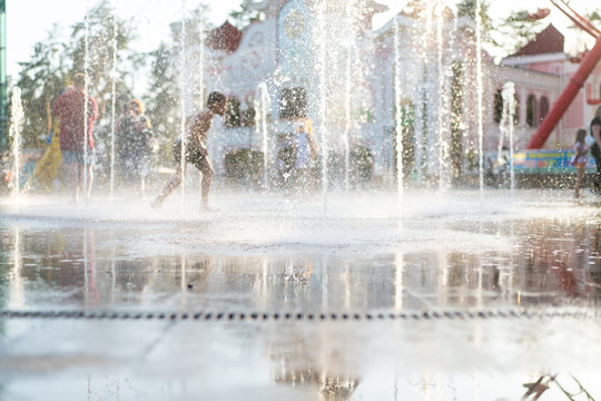Unrecognizable Happy kids have fun playing in city dry water fountain on hot summer day