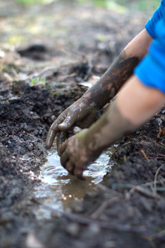 Fun child playing in mud pond created with hands, backyard