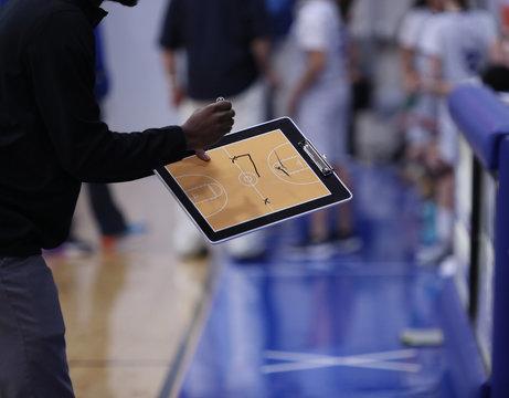 A girls basketball coach diagrams a play