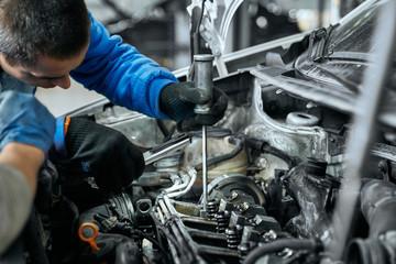 Auto mechanic in blue uniform replacing glow plugs in engine Fotomurales