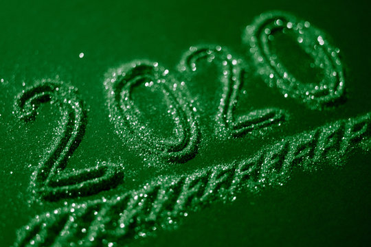 Christmas background with a flickering inscription 2020, green tone.