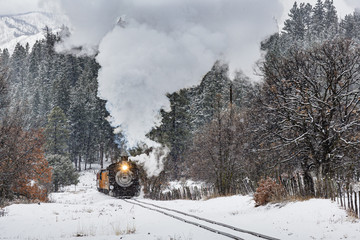 Snow Train. Vintage Steam Train Billowing Smoke as it Moves Through the Mountains.