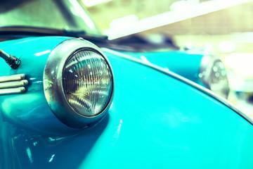 Fond de hotte en verre imprimé Vintage voitures close up eyes circle light bulb of blue vintage car .