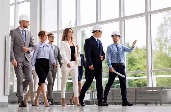 architecture, construction business and building concept - happy group of architects in helmets with blueprint walking along office building
