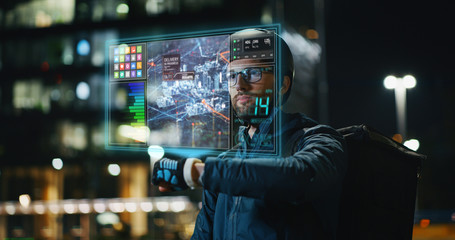 Portrait of an young delivery courier with bicycle is touching a futuristic screen with augmented reality hologram maps to view the addresses of customers in the evening in a city center.