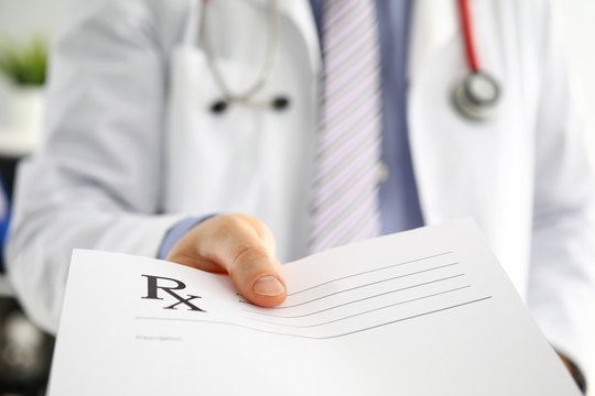 Male medicine doctor hand hold and give prescription form to patient